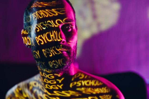 Jovem adulto com a palavra psicologia no rosto no escuro.