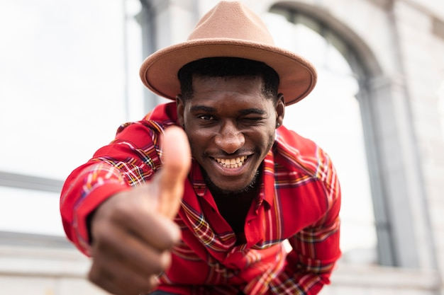 Jovem adulto com camisa vermelha gesto de polegar para cima