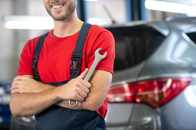 Jovem adulto confiante com uniforme de trabalho em pé perto de carros no showroom de carros