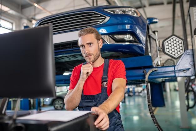 Jovem adulto confiante em uniforme de trabalho, trabalhando em carros