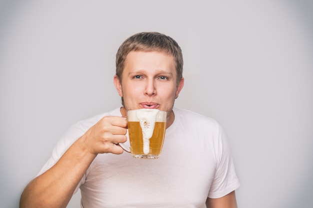 Jovem adulto de aparência europeia com uma caneca de cerveja em uma camiseta branca em um fundo isolado no estúdio