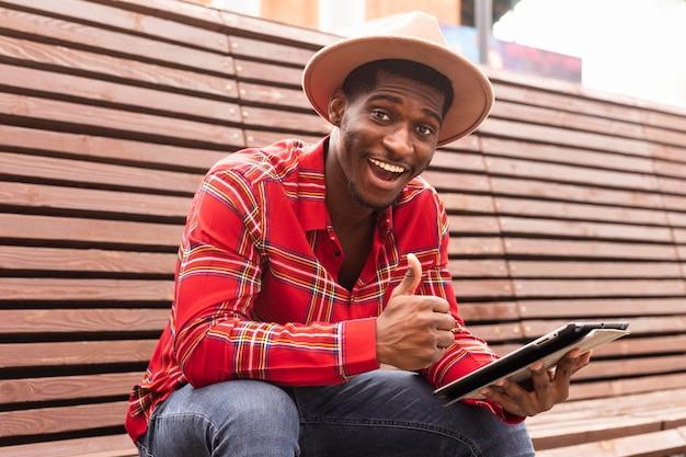 Jovem adulto de camisa vermelha com o polegar para cima