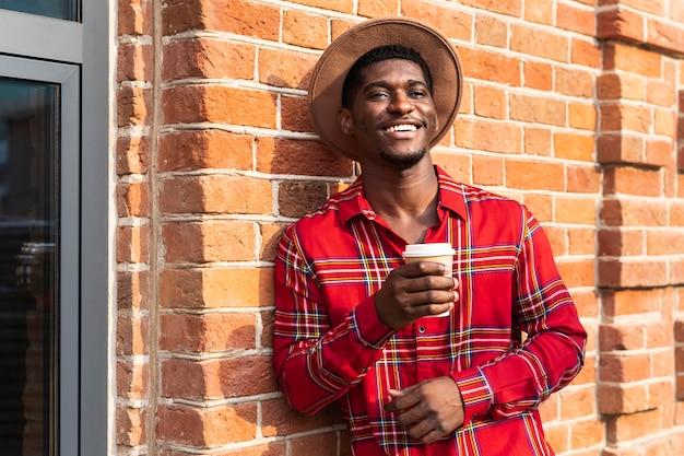 Jovem adulto de camisa vermelha sorrindo e apoiado em uma parede de tijolos