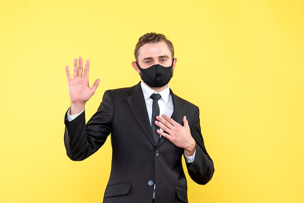 Jovem adulto de terno mostrando um gesto de despedida