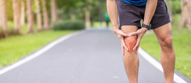 Jovem adulto do sexo masculino com dores musculares durante a corrida