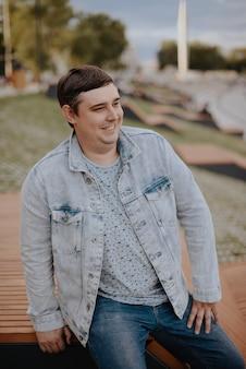 Jovem adulto em um parque da cidade com uma jaqueta jeans