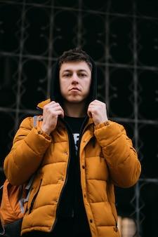 Jovem adulto em uma jaqueta amarela caminha em uma rua da cidade