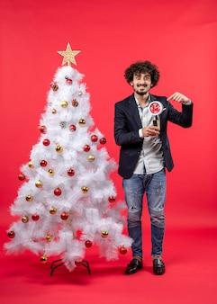 Jovem adulto empolgado segurando um relógio e uma taça de vinho e perto da árvore de natal no vermelho