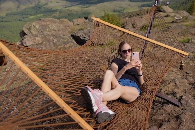 Jovem adulto feliz cabelos curtos raspada careca mulher atraente relaxando relaxe sentado na rede de cadeira de tecido no quintal em garen perto de casa. estilo de vida de descanso ao ar livre pacífico e idílico.