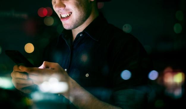 Jovem adulto feliz do sexo masculino usando um smartphone em uma paisagem urbana noturna