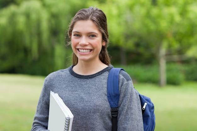 Jovem adulto feliz volta da escola enquanto segura um caderno
