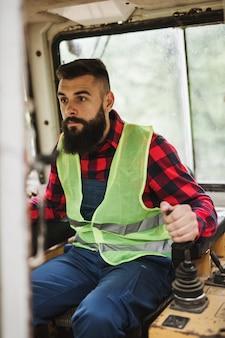 Jovem adulto lenhador ou lenhador trabalhando e usando ensacador na floresta