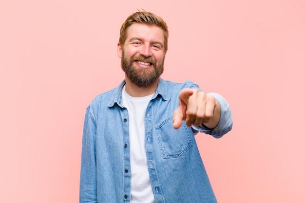 Jovem adulto loiro, apontando para a câmera com um sorriso satisfeito, confiante e amigável, escolhendo você