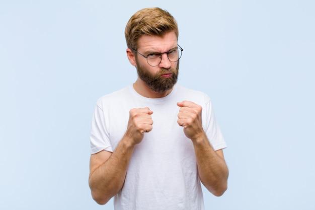 Jovem adulto loiro olhando confiante, irritado, forte e agressivo, com os punhos prontos para lutar na posição de boxe