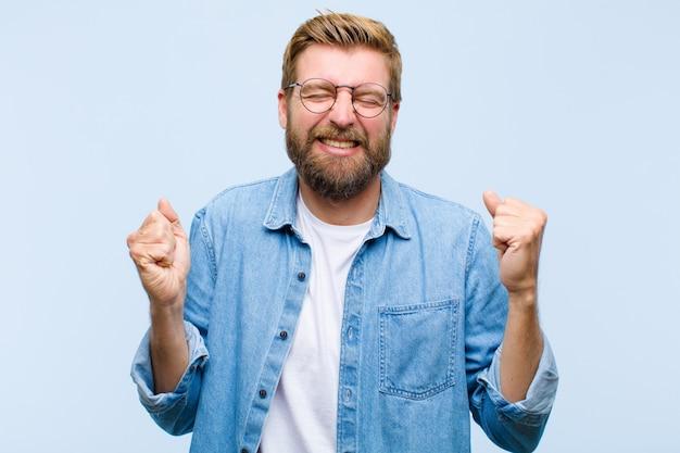 Jovem adulto loiro olhando extremamente feliz e surpreso, comemorando o sucesso, gritando e pulando