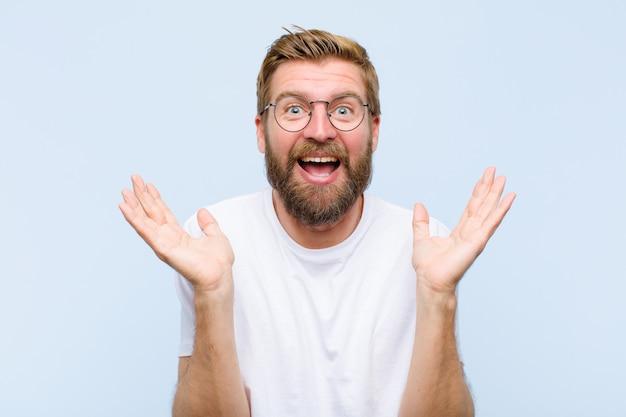 Jovem adulto loiro olhando feliz e animado, chocado com uma surpresa inesperada com as duas mãos abertas ao lado do rosto