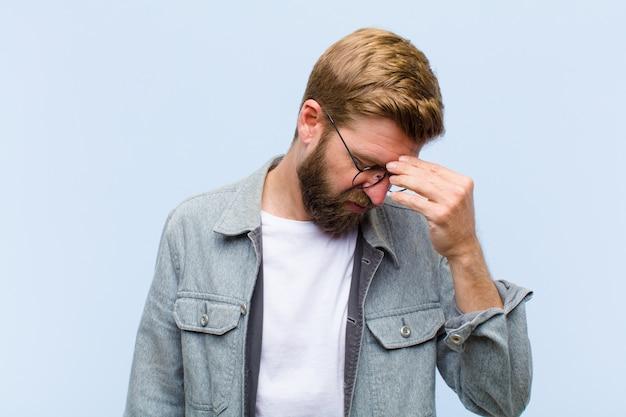 Jovem adulto loiro, sentindo-se estressado, infeliz e frustrado, tocando a testa e sofrendo de enxaqueca com fortes dores de cabeça
