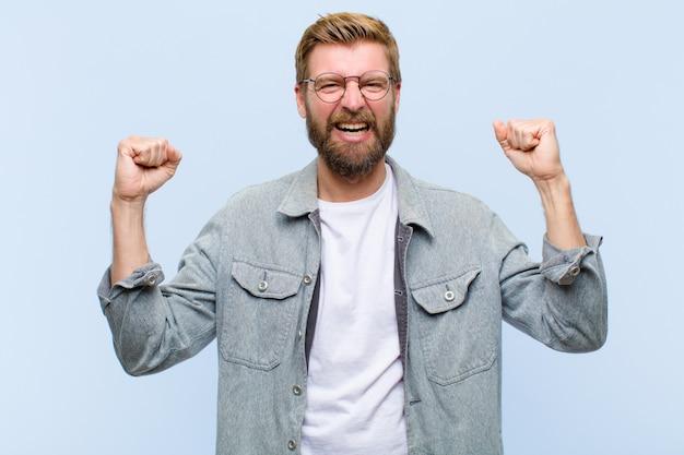 Jovem adulto loiro, sentindo-se feliz, positivo e bem sucedido, comemorando a vitória, conquistas e boa sorte