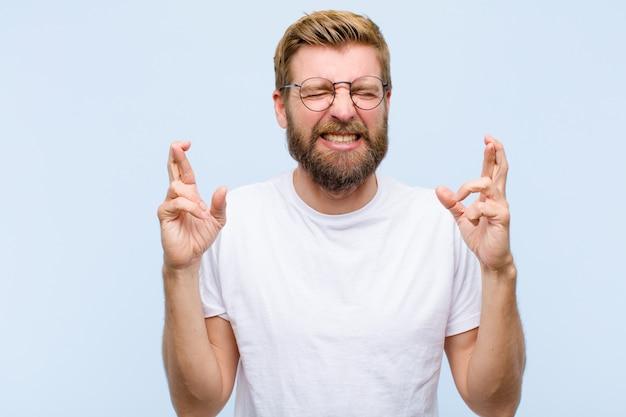 Jovem adulto loiro sorrindo e cruzando ansiosamente os dois dedos, sentindo-se preocupado e desejando ou esperando boa sorte