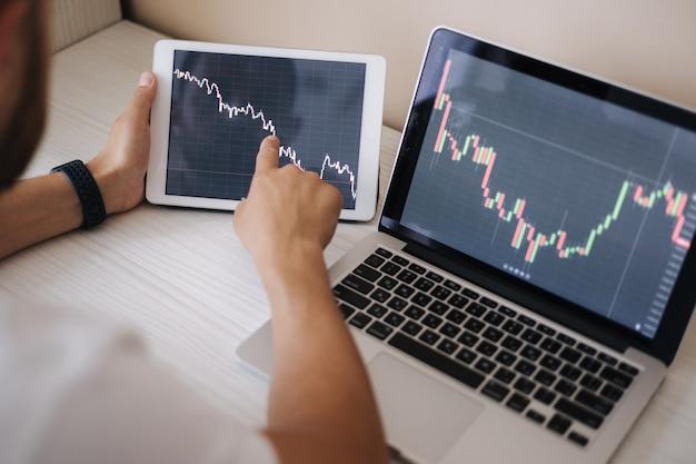 Jovem adulto negociando online com um tablet pc conectado ao mercado de ações.