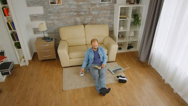 Jovem adulto ousado no chão de seu apartamento lendo um romance e tomando café em um domingo preguiçoso