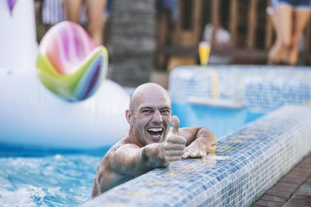Jovem adulto sorrindo feliz nadando na piscina na festa