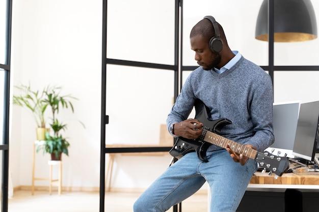 Jovem adulto tocando violão