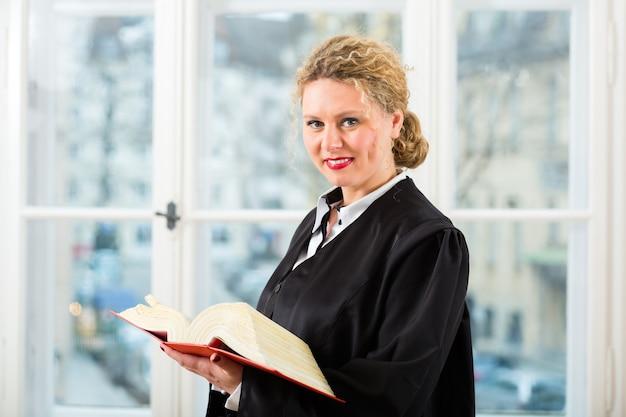 Jovem advogada trabalhando em seu escritório lendo um típico livro de direito