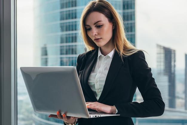 Jovem advogada trabalhando em seu luxuoso escritório, segurando um laptop de pé contra uma janela panorâmica com vista para o distrito financeiro.