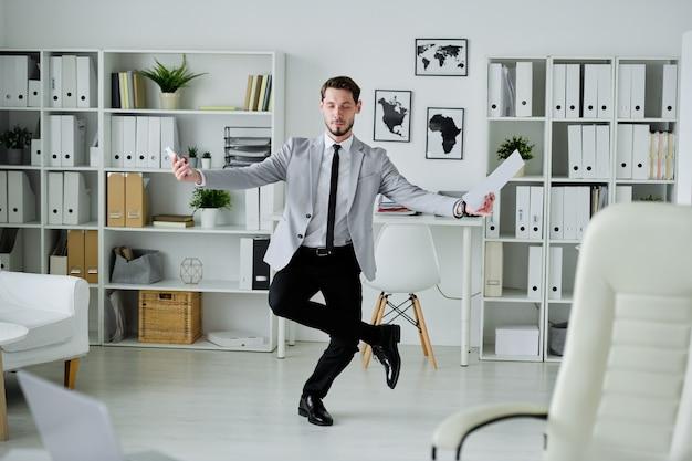 Jovem advogado da moda concentrado segurando um contrato e se equilibrando em uma perna para se concentrar nos pensamentos
