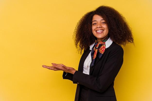 Jovem aeromoça afro-americana isolada em fundo amarelo, segurando um espaço de cópia na palma da mão.