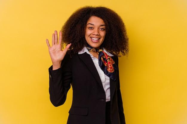 Jovem aeromoça afro-americana isolada na parede amarela, sorrindo alegre mostrando o número cinco com os dedos.