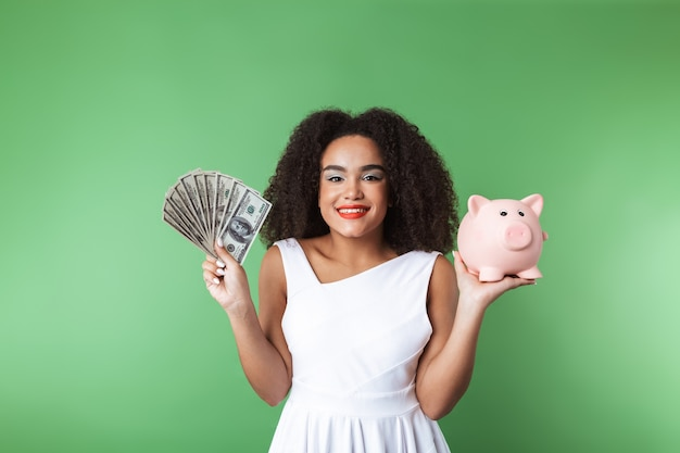 Jovem africana alegre com um vestido isolado, mostrando o cofrinho e as notas de dinheiro