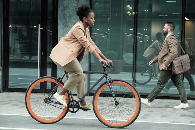 Jovem africana andando de bicicleta em direção ao trabalho pelas ruas da cidade