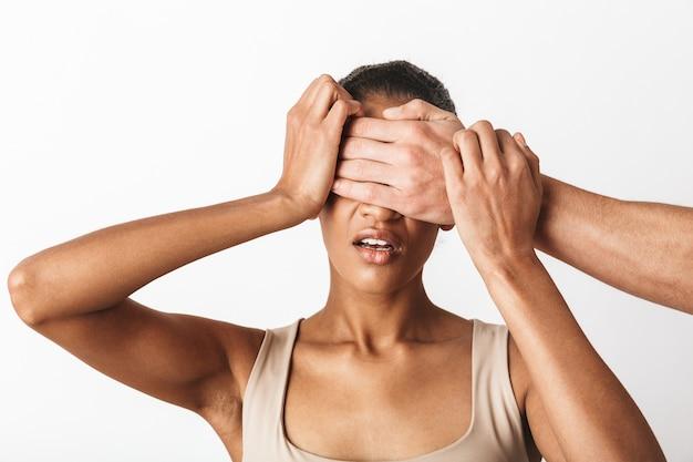 Jovem africana assustada sentada enquanto a mão de um homem fecha os olhos em branco