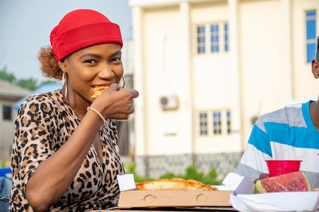 Jovem africana comendo pizza, sentada com um amigo