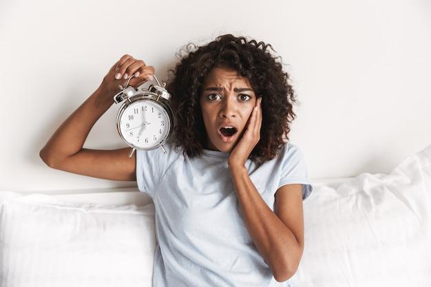 Jovem africana confusa mostrando o despertador