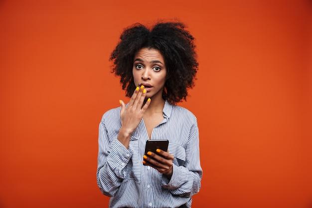 Jovem africana confusa usando o celular isolado sobre a parede vermelha
