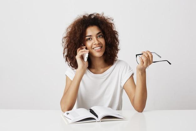 Jovem africana elegante dando um tempo no seu estudo, conversando com a mãe no telefone, discutindo sobre um novo namorado ou uma ligação do futuro empregador contratado para o primeiro emprego, tendo em vista um trabalho de marketing.
