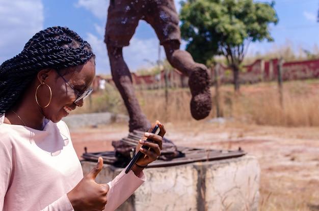 Jovem africana em pé no campo, felizmente operando seu telefone e fazendo sinal de positivo com o polegar