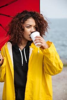 Jovem africana encaracolada concentrada caminhando ao ar livre e bebendo café.
