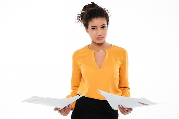 Jovem africana encaracolada confusa em pé com documentos