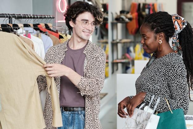Jovem africana escolhendo uma roupa nova para si mesma com a ajuda de uma vendedora no shopping