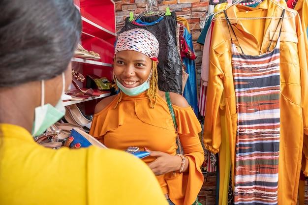 Jovem africana fazendo compras em uma butique local, sorrindo e conversando com alguém