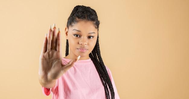 Jovem africana fazendo gesto de parar o racismo