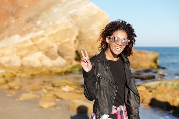 Jovem africana feliz caminhando ao ar livre na praia.