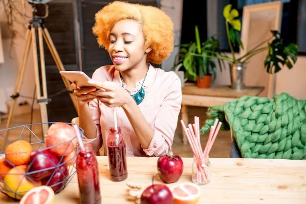 Jovem africana fotografando com frutas e smoothies de telefone, sentada dentro de casa, no aconchegante interior de sua casa