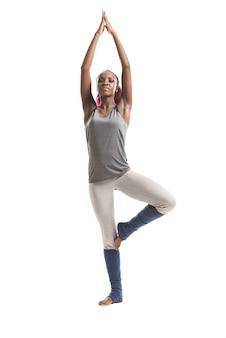 Jovem africana na posição de yoga da árvore