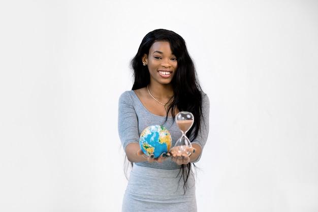 Jovem africana sorridente no vestido cinza tem nas mãos globo do mundo terra e ampulheta