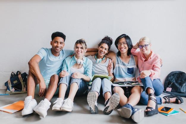Jovem africano alegre de tênis branco, abraçando seus amigos de universidade sentados no chão com a mochila. retrato interno de estudantes sorridentes, descansando depois das aulas e posando com prazer.